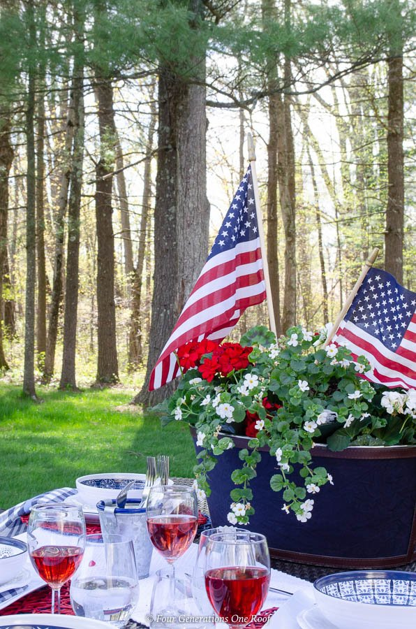Classy Patriotic Decor Ideas on our Patio patriotic outdoor table on lawn, ice bucket centerpiece filled with geraniums and flags, red striped tablecloth, melamine blue and white dishes, wine glass filled with red wine
