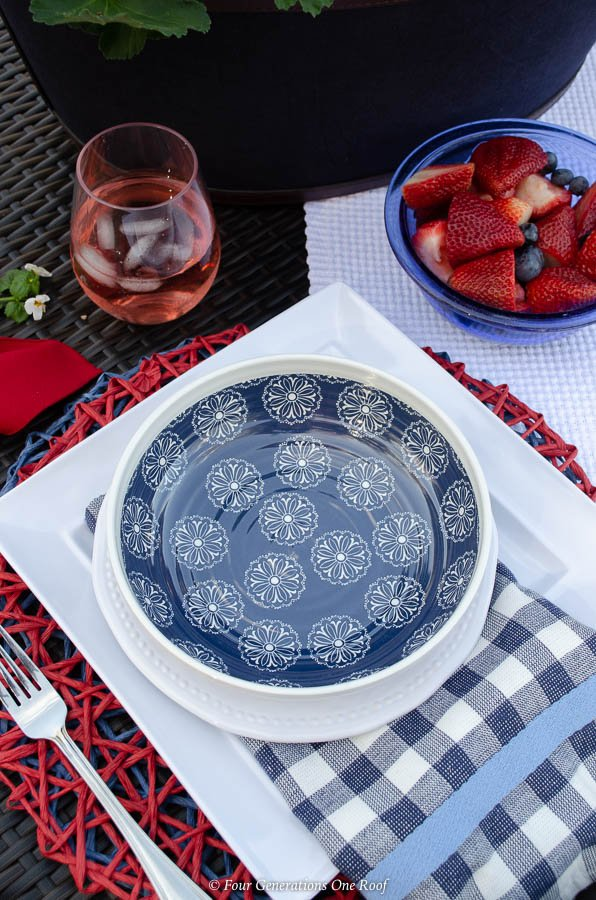 Classy Patriotic Decor Ideas on our Patio patriotic outdoor table on law, ice bucket centerpiece filled with geraniums and flags, red striped tablecloth, melamine blue and white dishes, wine glass filled with red wine