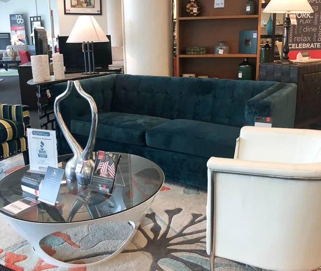 used velour blue tufted couch, glass coffee table, white modern chair