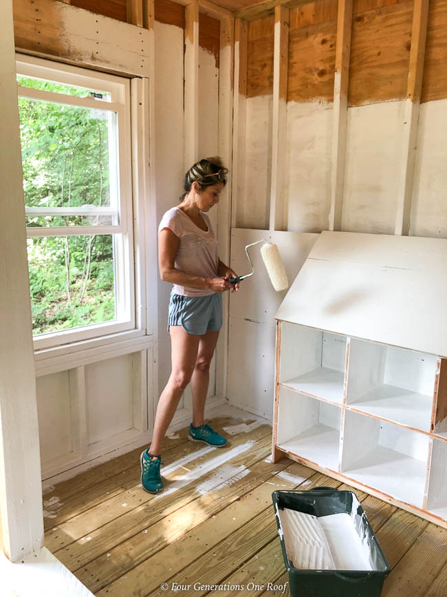 jessica bruno painting the inside of a chicken coop white