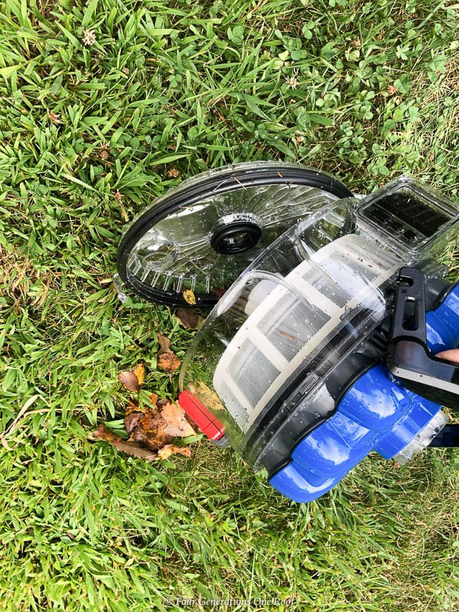 Hayward AquaVac 6 Series robotic pool cleaner filter being dumped on grass