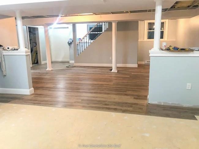 Harvest Oak Rigid Core Vinyl Flooring in basement over cement, white decorative columns over lally columns