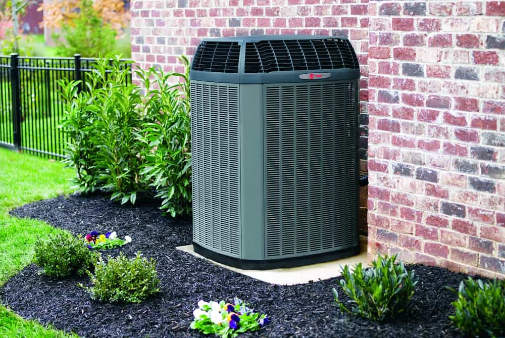 Trane Air Conditioner outside in flower bed brick house