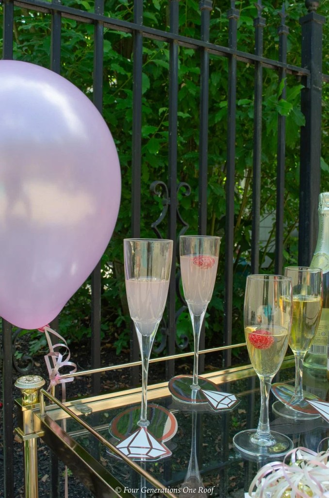 gold bar cart, pink balloon, champagne glasses filled with champagne and raspberry