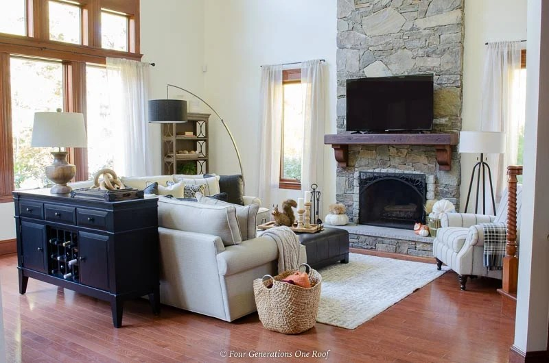 Neutral living room, tv on mantel, cathedral ceiling, white sectional, black sofa wine server, stained trim
