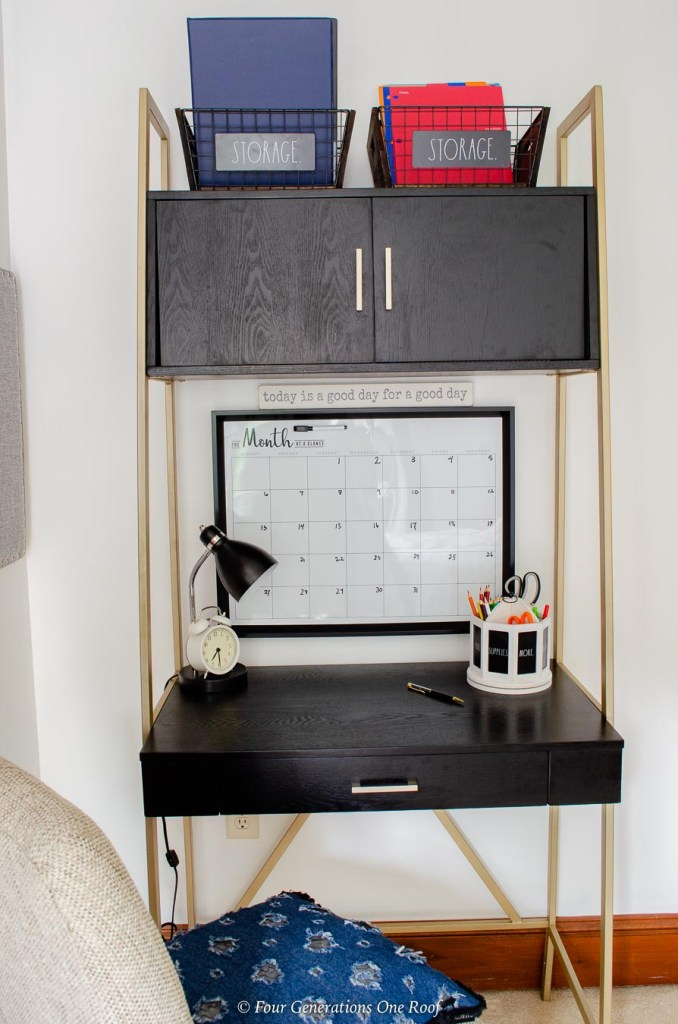 teenager bedroom workspace, black and gold tall desk, built in cabinets, chair, wall calendar