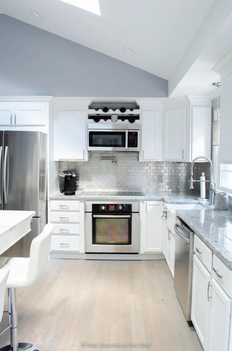 split level house vaulted ceiling, white kitchen, stainless steel appliances, driftwood flooring