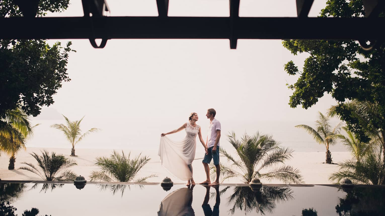 Woman in white lace dress and man walk along edge of reflection pool