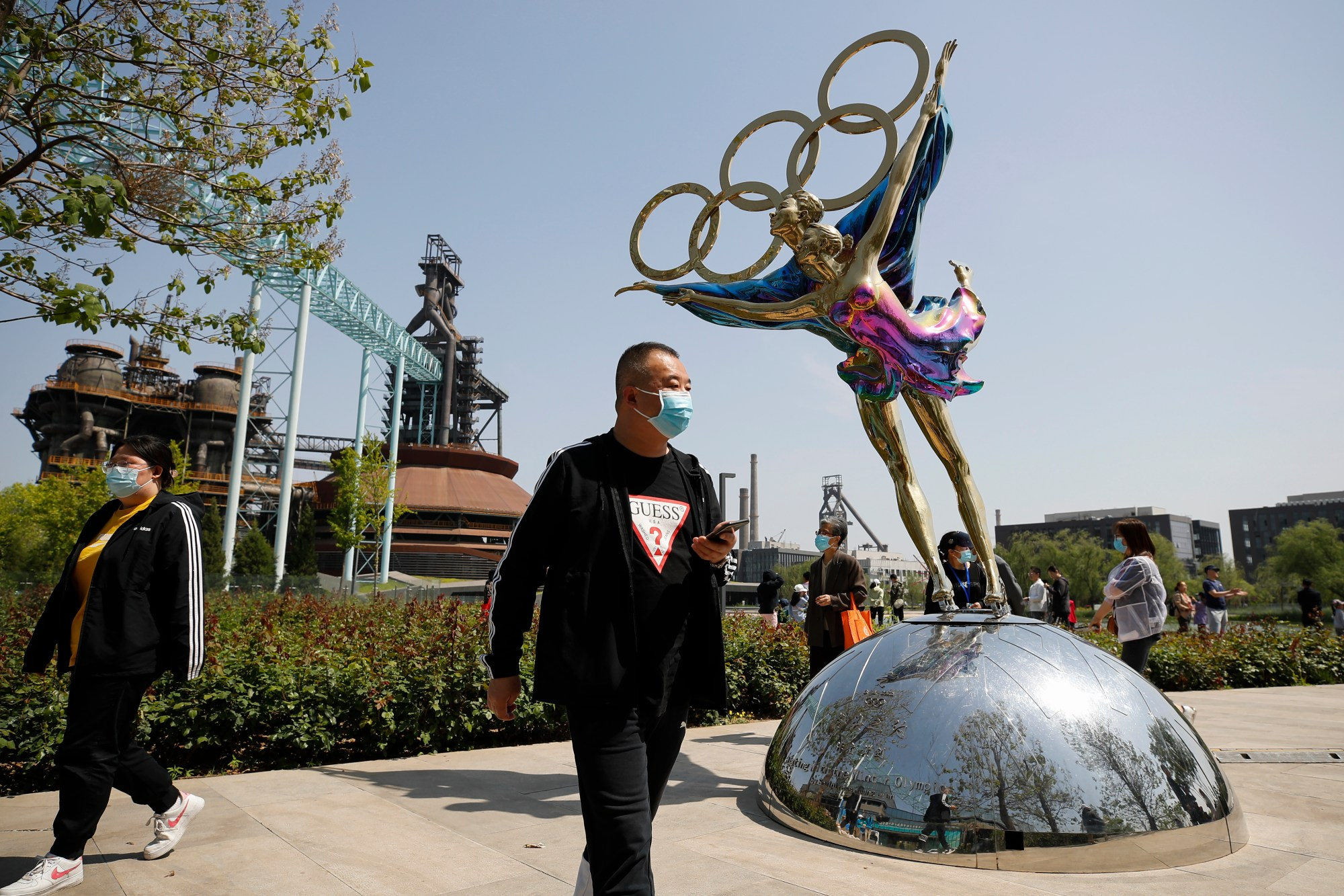 Visitors wearing face masks to help curb the spread of the coronavirus walk by a statue featuring Winter Olympics figure skating on display at the Shougang Park in Beijing, Sunday, May 2, 2021. (AP Photo/Andy Wong)