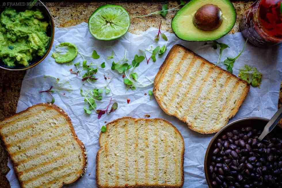 ingredients to prepare avocado toast -  bread slices, lemon, microgreens, avocado butter, whole avocado, hot sauce, black beans.