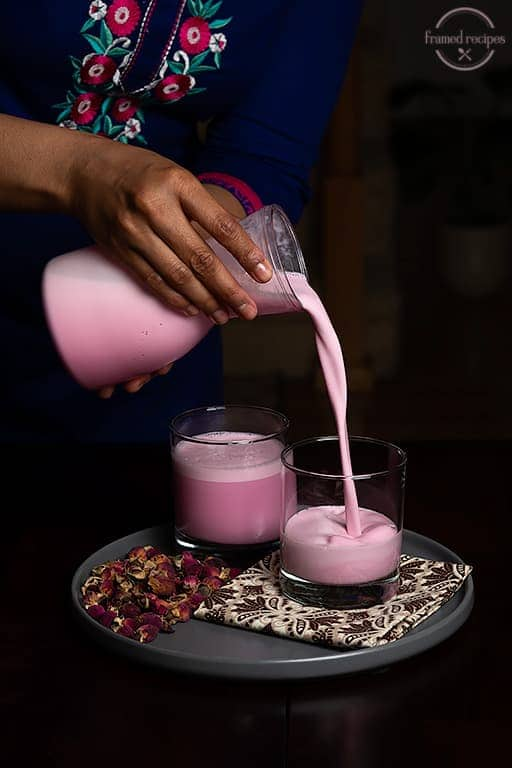 lady pouring rose milk into serving glasses'.