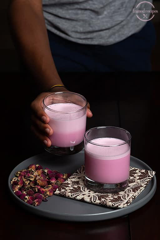 reaching out to grab a cup of rose milk.