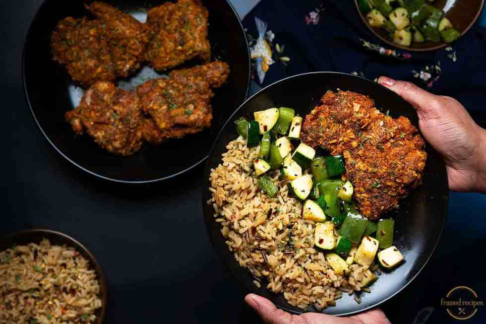 Spicy_Oats_Crusted_Chicken_Thighs_serving_suggestion_of_vegetables_and_rice_hand_holding_plate