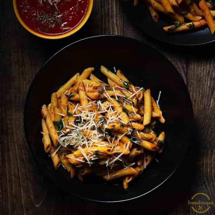 Cajun Spiced Spinach pasta in a black bowl with marinara sauce