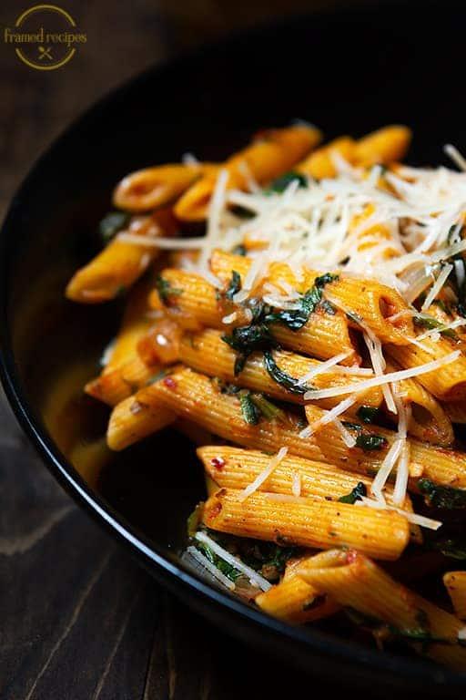 Cajun Spiced Spinach pasta in a black bowl closeup vertical picture