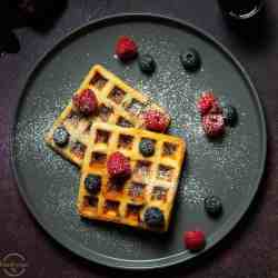YEASTED OATS WAFFLES GARNISHED WITH BERRIES AND POWDERED SUGAR