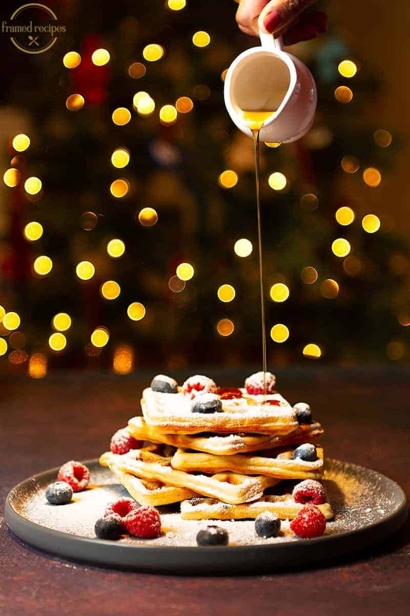 Yeasted_Oats_Waffles_MAPLE SYRUP_POURING_WITH_CHRISTMAS_LIGHTSIN THE BACKGROUND