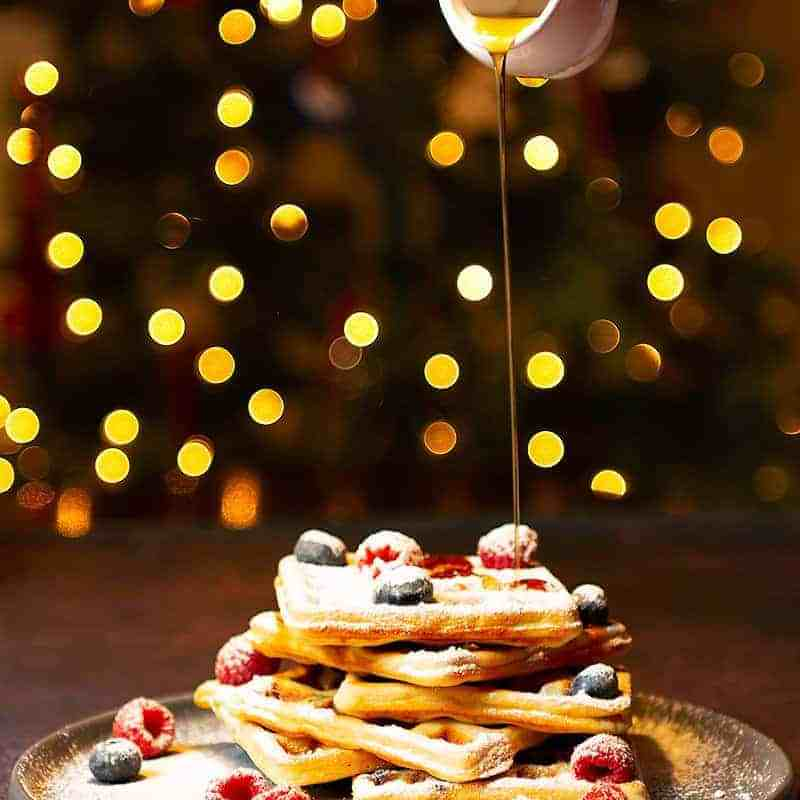 Yeasted Oats Waffles_MAPLE SYRUP_POURING_WITH_CHRISTMAS_LIGHTSIN THE BACKGROUND