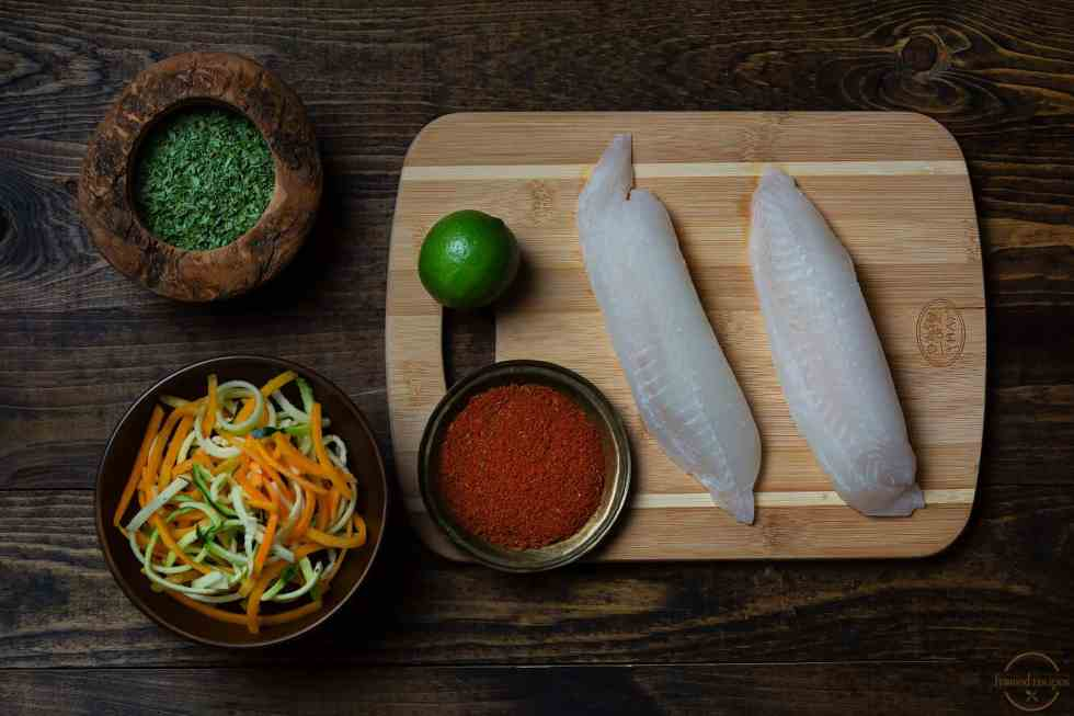 ingredients to make blackened tilapia on stovetop - fish fillet, spice rub, dried parsley for garnish, lemon and spiralized vegetable to serve.