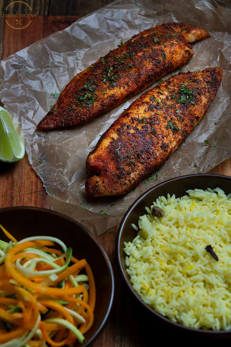 tilapia cooked on stovetop with blackened spice rub served with saffron rice and spiralized vegetables.