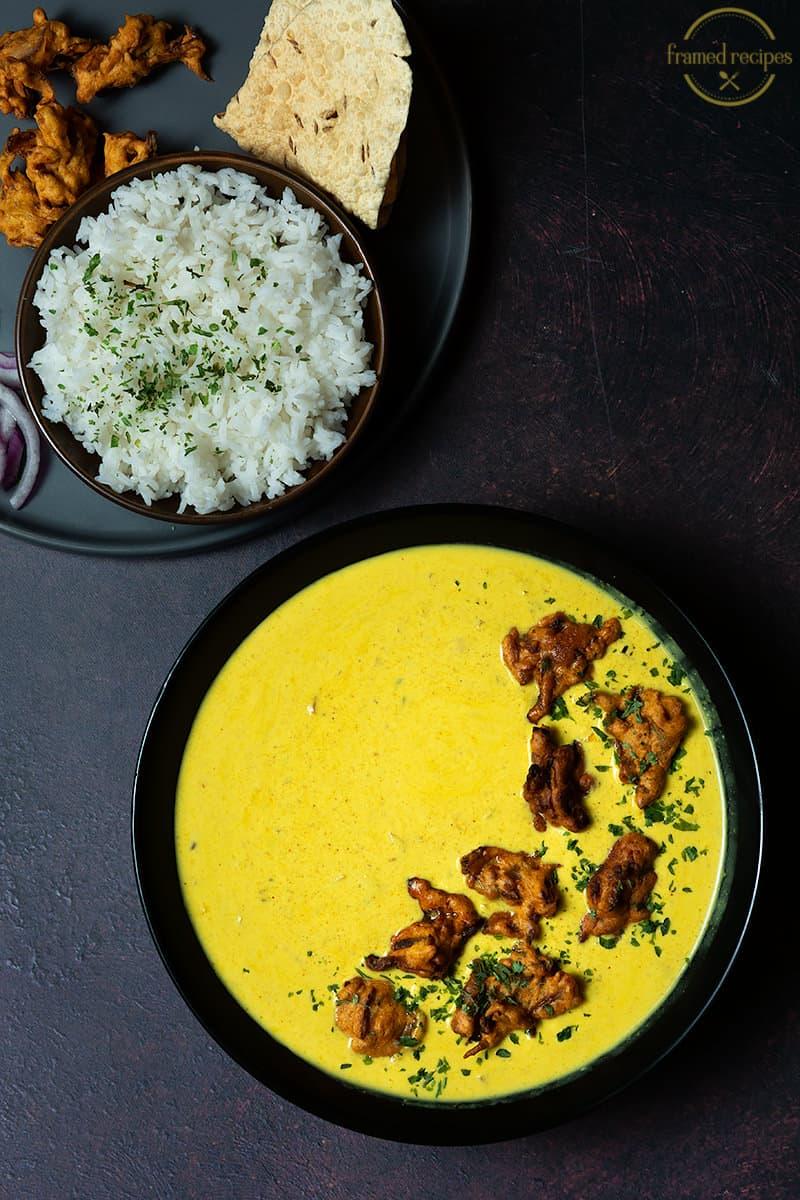 kadhi pakora served with rice, papad and onion rings.