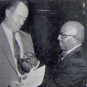 Dr. Charles R. Cephas, Grand President of Chi Delta Mu, pins the fraternity's badge on senator Hubert H. Humphrey.