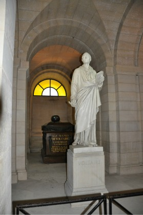 Voltaire stands in front of his tomb