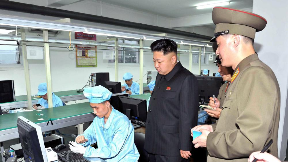 Le leader nord-coréen Kim Kong-Un inspecte le processus de production d'un téléphone mobile, dans une usine du pays. Le cliché, non daté, a été diffusé le 11 août 2013 par l'agence d'information officielle KCNA.