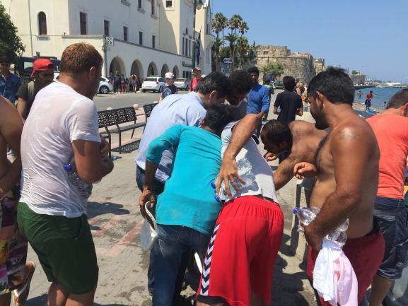 Nasser, touriste allemand en vacances à Kos (Grèce), le 20 août 2015, assailli de migrants venant prendre les bouteilles d'eau qu'il leur donne.