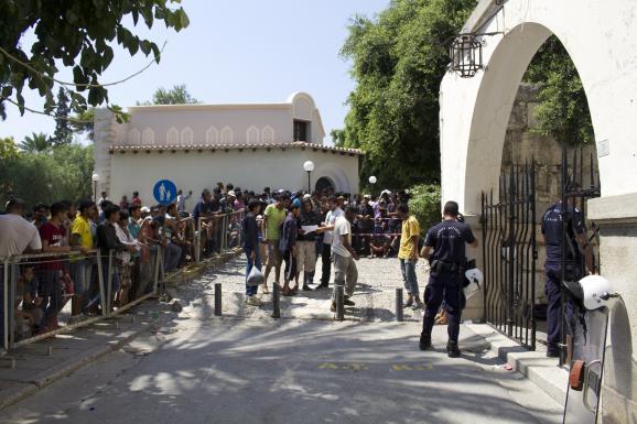 Des migrants attendent de pouvoir se faire enregistrer au commissariat de police de Kos (Grèce), le 20 août 2015.