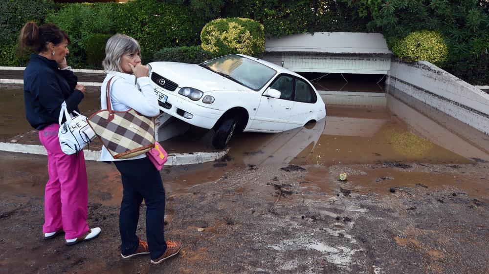 Des habitantes deMandelieu-la-Napoule (Alpes-Maritimes) passent devant un parking souterrain rempli de boue après les orages violents qui ont touché le département, le 4 octobre 2015.