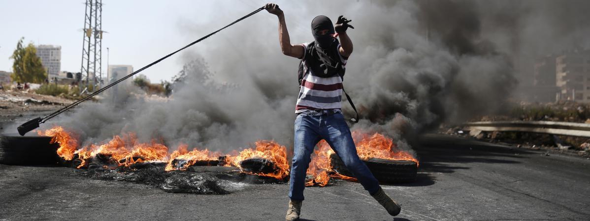 Un Palestinien affronte à coup de jets de pierre des soldats israéliens le 11 octobre 2015 près deRamallah en Cisjordanie.
