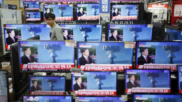 Un vendeur regarde des écrans de télévision retransmettant des images provenant de Corée du Nord et montrant un possible essai nucléaire, le 6 janvier 2016 à Séoul (Corée du Sud).