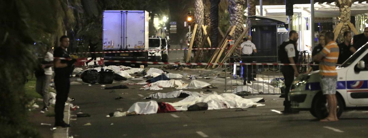 Des corps recouverts d'un drap sur la promenade des Anglais, à Nice (Alpes-Maritimes), après l'attaque d'un chauffeur à bord d'un camion, le 14 juillet 2016.