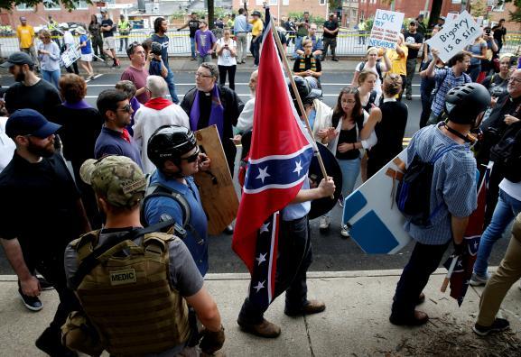 Un manifestant porte un drapeau confédéré dans les rues de Charlottesville, samedi 12 août 2017.