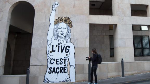 """Un passant s\'arrête devantune œuvre du street-artist Emmanuel Mahn indiquant \""""L\'IVG, c\'est sacré\"""", à Marseille (Bouches-du-Rhône), le 8 mars 2017."""