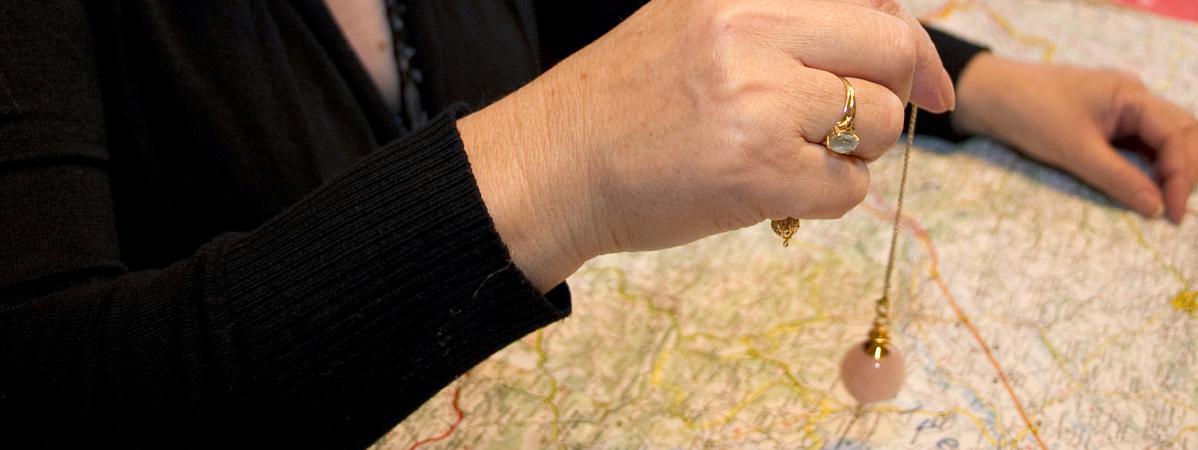 Une cartomancienne utilise un pendule au dessus d\'une carte de France le 22 décembre 2011 au Vernet (Haute-Garonne).