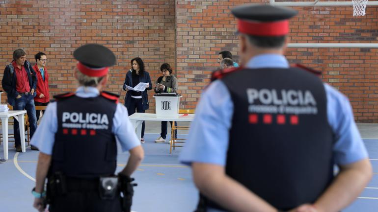 Des policiers catalans entrent dans un bureau de vote pour le référendum d\'autodétermination, le 1er octobre 2017, à Figueras (Espagne).