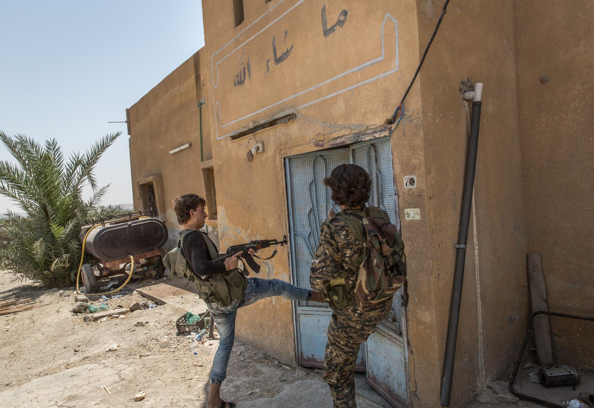 Deux combattants arabes de la Brigade de la liberté, composante des FDS, défoncent la porte d\'une maison abandonnée, à Raqqa (Syrie), le 5 juillet 2017.