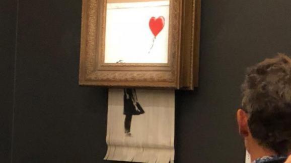 """La \""""Fille au ballon\"""" de Banksy, sort de son cadre, chez Sotheby\'s, à Londres (Royaume-Uni), le 5 octobre 2018."""