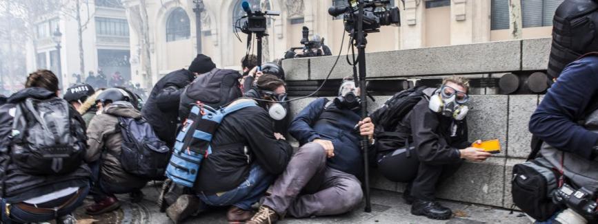 """Des journalistes se mettent à terre pour éviter les tirs de flash-balls lors de la mobilisation des \""""gilets jaunes\"""" à Paris, le 8 décembre 2018."""