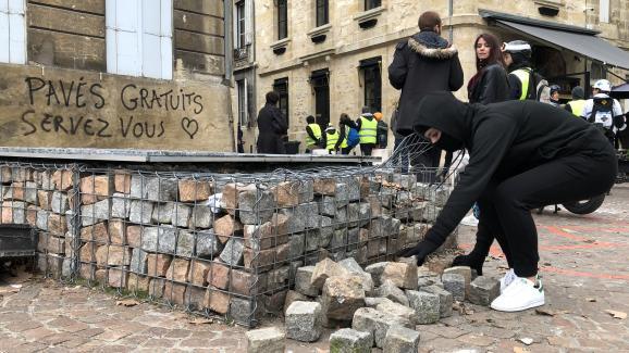 """Une femme ramasse des pavés lors de la manifestation des \""""gilets jaunes\"""" à Bordeaux, le 12 janvier 2019."""