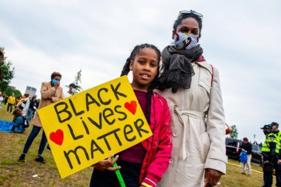 """Une femme et sa fille portent une pancarte \""""Black lives matter\"""", lors d\'un rassemblement à Amsterdam (Pays-Bas), le 10 juin 2020."""