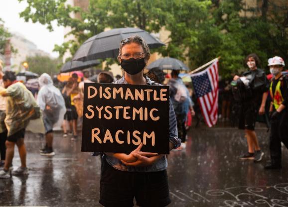 """Une personne porte une pancarte contre le \""""racisme systémique\"""" près de la Maison Blanche à Washington (Etats-Unis), lors d\'une manifestation contre les violences policières et le racisme, le 5 mai 2020."""