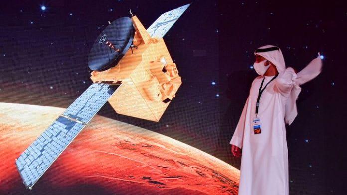 Un Emirati passe devant une illustration de la sonde Hope au Centre spatial Mohammed Bin Rashid, à Dubaï, le 19 juillet 2020. (GIUSEPPE CACACE / AFP)