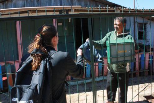A agente de combate a endemias entrega um saco plástico para o morador João Idalece fazer a vistoria de possíveis focos de dengue no quintal