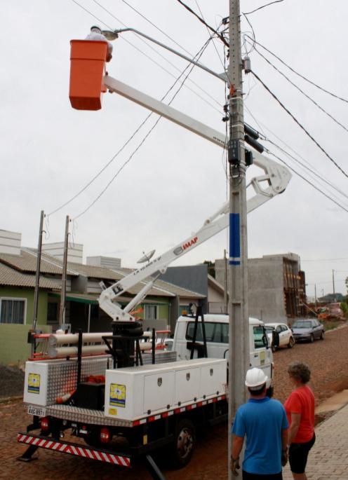 Dona Lurdes e o auxiliar Luis observam a troca de um reator que há um mês estava danificado, no bairro São Cristóvão