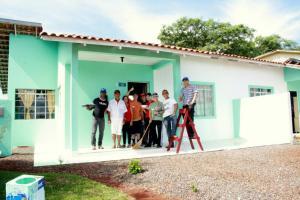 O casal Derci e Maria Terezinha, moradores do Condomínio do Idoso, com os alunos da escola de soldados da PM posam para foto em frente a casa com nova pintura
