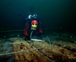 View on the wreck discovered in the ancient port of the Island of Antirhodos after the removal of sediment. The analysis of the in mud well preserved wooden remains and of parts of the cargo shows that this ship might date back to the 1st century BC. With