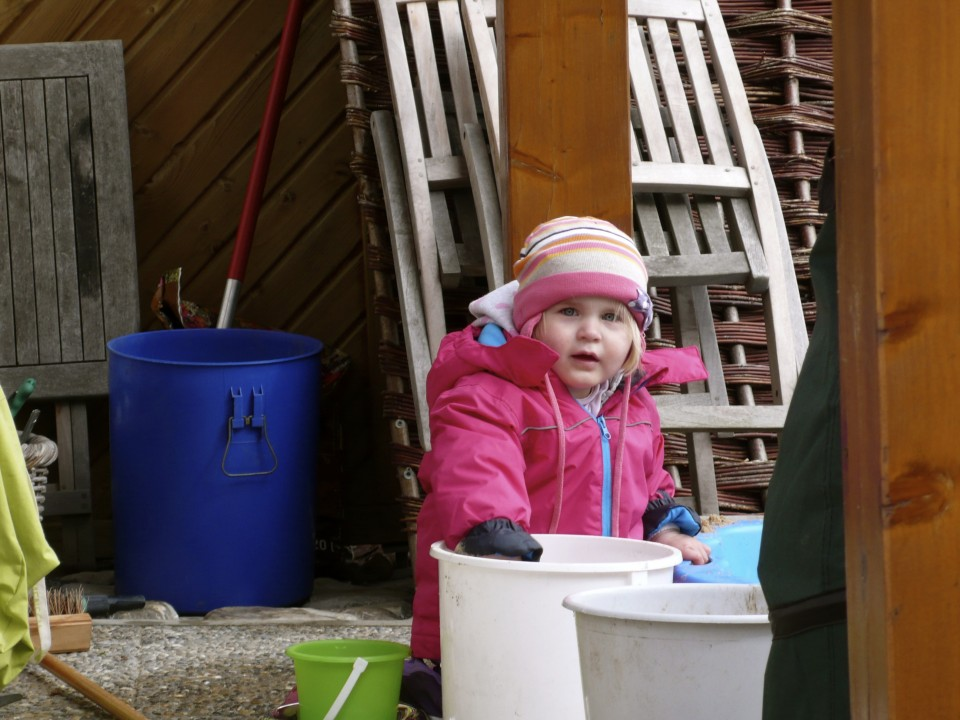 Adorable little girl making imaginary mud pies as her mother did some yard work.